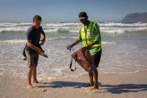 Vista frontale dei volontari afroamericani maschi che puliscono la spiaggia in una giornata di sole — Foto stock