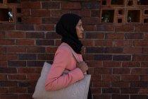 Vista lateral de pensativa séria mulher de raça mista andando na calçada ao lado de um tempo segurando sua bolsa — Fotografia de Stock