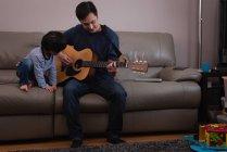 Vue de face d'un père asiatique jouant de la guitare pour son fils sur le canapé à la maison — Photo de stock