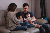 Vista lateral de una familia asiática feliz sentada en el sofá y abrazándose en casa - foto de stock