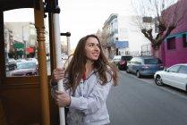 Opinião dianteira a mulher caucasiano nova feliz que pendura fora do veículo movente na cidade — Fotografia de Stock