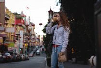 Side view of beautiful young Caucasian woman having coffee while standing on street in city — Stock Photo