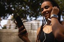 Visão de baixo ângulo da jovem mulher de raça mista usando fones de ouvido enquanto usa telefone celular na rua da cidade — Fotografia de Stock