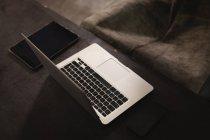 Крупный план ноутбука и цифрового планшета на полу в гараже — стоковое фото