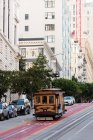 Tram in movimento su una pista dall'altra parte della strada della città in una giornata di sole — Foto stock
