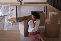 Low angle view of thoughtful mixed-race businesswoman having coffee while sitting on floor against cartons in modern office — Stock Photo