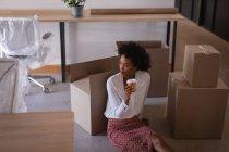 Vue à angle bas d'une femme d'affaires métissée réfléchie prenant un café assis sur le sol contre des cartons dans un bureau moderne — Photo de stock