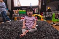 Retrato de un pequeño bebé asiático lindo mirando a la cámara y sentado en la alfombra en casa - foto de stock