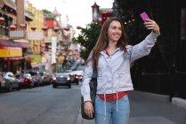Vue de face de belle jeune femme caucasienne prenant selfie tout en se tenant sur le côté promenade dans la ville — Photo de stock