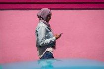 Vista lateral de la hermosa mujer de raza mixta utilizando el teléfono móvil mientras camina desde el callejón en un día soleado - foto de stock