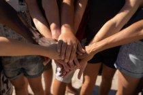 Mittelteil der Gruppe von Freiwilligen, die Hände stapeln sich am Strand — Stockfoto