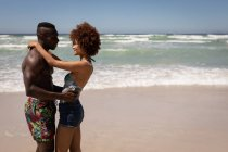 Side view of happy multi ethnic couple embracing each other on the beach on sunny day — Stock Photo