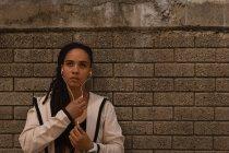 Vista frontale della giovane donna di razza mista che ascolta musica sulle cuffie mentre si appoggia a un muro in strada — Foto stock