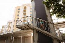 Vista a basso angolo della giovane donna di razza mista che si esercita sulle scale in città — Foto stock