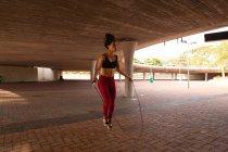 Frontansicht einer jungen Mischlingshündin, die mit Springseil unter einer Brücke in der Stadt trainiert — Stockfoto