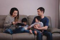 Vista frontal de la familia asiática disfrutando juntos mientras se sientan en el sofá con tableta y maíz en casa - foto de stock