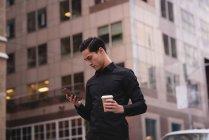 Vue de face du bel homme asiatique utilisant un téléphone mobile dans la rue tout en prenant un café — Photo de stock