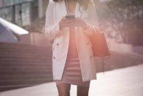 Section moyenne de femme utilisant le téléphone intelligent tout en restant sur le trottoir un jour ensoleillé — Photo de stock