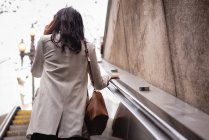 Rear view of Asian woman talking on mobile phone on escalator — Stock Photo