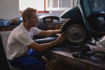 Side view of Caucasian male bike mechanic repairing motorbike tire in garage — Stock Photo