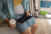 Partie médiane de l'homme utilisant un ordinateur portable tout en prenant un café dans un atelier — Photo de stock