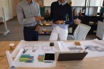 Metà sezione di uomini d'affari di razza mista che interagiscono tra loro su stampa blu in un ufficio moderno. Si stringono la mano — Foto stock