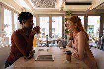 Вид сбоку на молодых подруг смешанной расы, взаимодействующих друг с другом за чашечкой кофе в кафе — стоковое фото