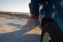 Низкая часть пары на пляже в машине в солнечный день — стоковое фото