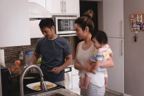 Side view of Asian mother and son looking at Asian father while making pancakes in kitchen at home — Stock Photo