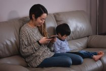Side view of a happy young Asian mother using mobile phone while son using digital tablet on sofa at home — Stock Photo