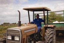 Vue de face du tracteur routier afro-américain avec remorque verte à la ferme — Photo de stock