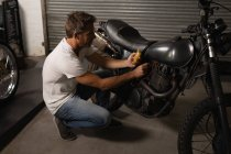 Side view of Caucasian male bike mechanic checking battery of bike with multimeter in garage — Stock Photo