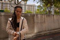 Vista frontal da jovem mulher de raça mista usando smartwatch na rua da cidade — Fotografia de Stock