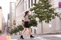 Vista lateral da mulher asiática usando telefone celular enquanto caminha da rua no pavimento — Fotografia de Stock