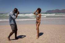 Vista lateral do homem afro-americano tirando fotos de uma mulher muito mista com câmera digital na praia em um dia ensolarado — Fotografia de Stock