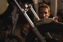 Вид на Кавказький чоловік велосипед механік ремонт бруду велосипеда в гаражі — стокове фото