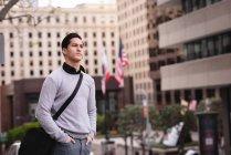 Vue de face de l'homme asiatique réfléchi debout sur la rue — Photo de stock