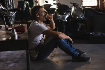 Side view of Caucasian bike mechanic sitting on the floor while having coffee in garage — Stock Photo