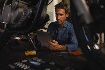 Vista frontal do mecânico de bicicletas masculino caucasiano usando tablet digital enquanto trabalhava na garagem — Fotografia de Stock