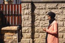 Vista lateral da mulher de raça mista usando telefone celular enquanto está em frente à parede na rua — Fotografia de Stock
