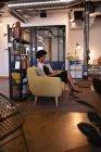 Вид сбоку красивой бизнесвумен смешанной расы, использующей ноутбук в офисе, сидя на современном желтом диване на фоне мебели — стоковое фото