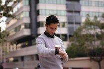 Vista frontal del hombre asiático guapo usando reloj inteligente mientras toma café en la calle - foto de stock