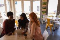 Vista laterale di giovani amiche di razza mista che interagiscono tra loro durante l'utilizzo di tablet digitale in un caffè — Foto stock