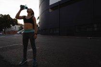 Vista frontale di stanco giovane gara donna che beve acqua in strada — Foto stock