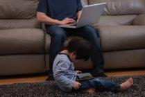 Sección baja de padre asiático usando su computadora portátil en el sofá mientras su hijo está usando una tableta digital en casa - foto de stock