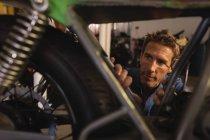Вид на Кавказький чоловік велосипед механік ремонт велосипеда в гаражі на семінарі — стокове фото