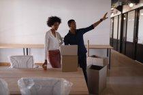 Vista laterale di giovani imprenditori di razza mista che discutono tra loro nell'ufficio moderno — Foto stock