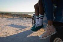 Bassa sezione di coppia in spiaggia in auto in una giornata di sole — Foto stock