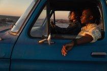 Вид сбоку романтической афроамериканской пары за рулем автомобиля на пляже на закате — стоковое фото