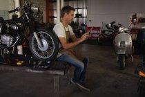Вид збоку Кавказького велосипеда механік з використанням цифрової таблетки, сидячи на столі в гаражі — стокове фото